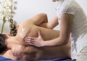 Chiropractor massaging a man's back