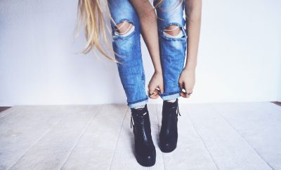 woman tucking her jeans into her boots