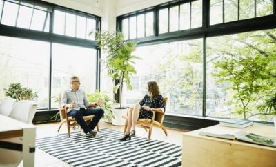 two people sitting in a an office with plants