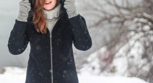 a faceless woman wearing winter coast in the snow