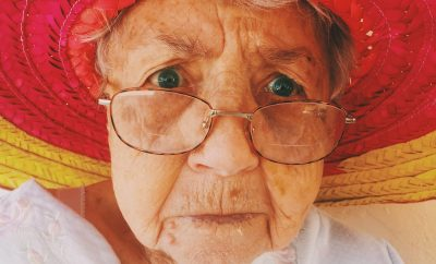 old lady wearing a red hat and glasses