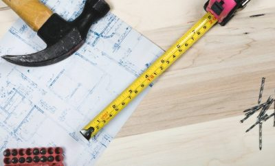 hammer, metric tape and a houe plan