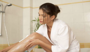 How to Keep Your Style Game High While Travelling- Woman in a white robe shaving her legs