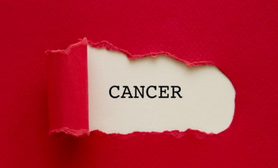 red paper torn back to reveal word cancer