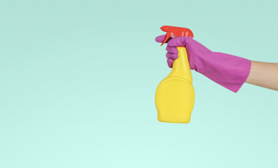 Purple gloved hand holding a cleaning spray bottle