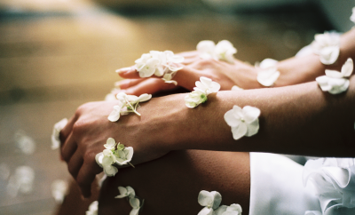 woman's hands covered in white flowers