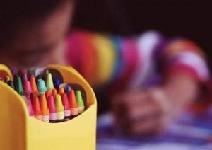 Crayons and child using them to draw