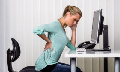 woman at a desk feeling her achy back