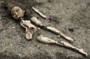 Old, broken discarded doll