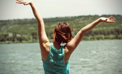woman by the sea with arms raised up