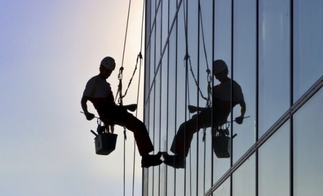Window cleaner hanging by ropes