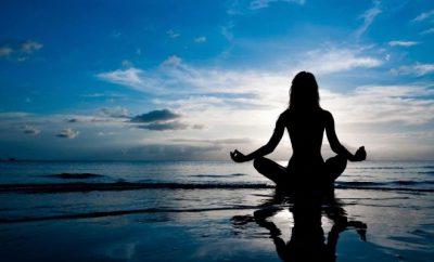 woman at the beach meditating