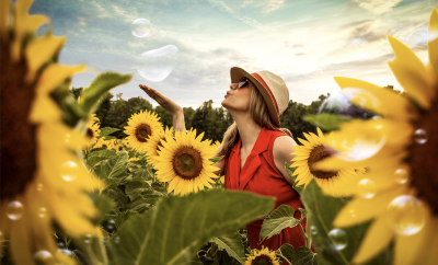 lady among sunflowers in a sunny day