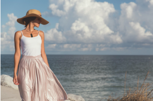 Lady walking on the beach wearing a hat