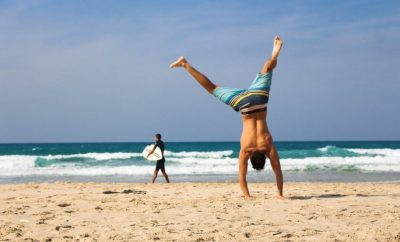 man doing cartwheels at the beach