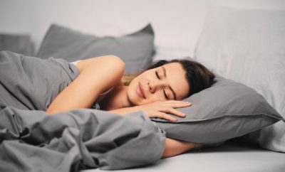 woman asleep in a bed with grey sheets