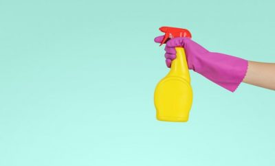 yellow cleaning spray bottle and purple gloves