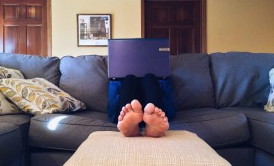 Feet of a man working on a laptop in the couch