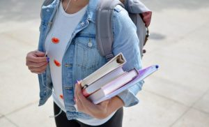 girls holding books on her hands