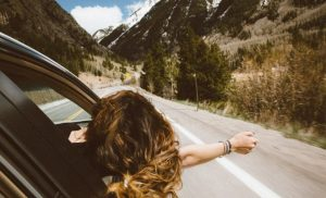 woman with head out of car window, road trip