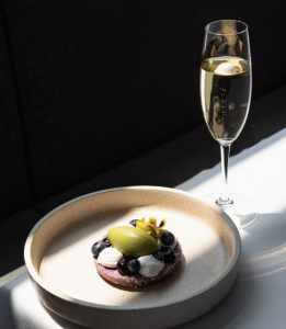 Aqua Dining - plate accompanied with a glass of champagne