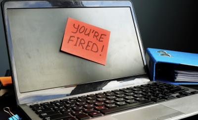 "Computer with a sticky note ""You're fired"""