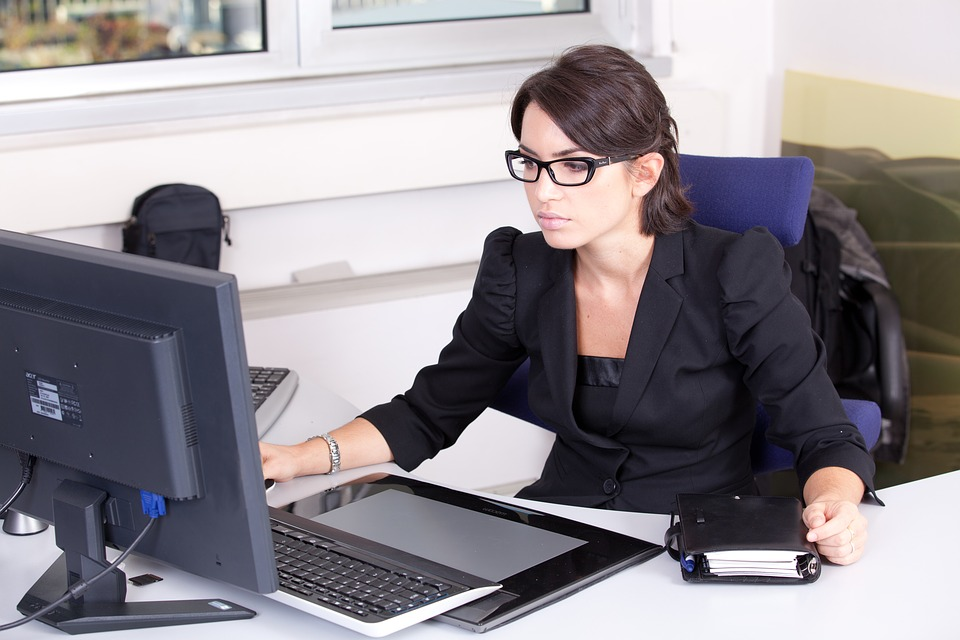 woman wearing glasses in front of computer