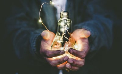 Man holding in his hands a lit lightbulb