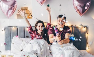 Couple in bed celebrating an occasion with ballons