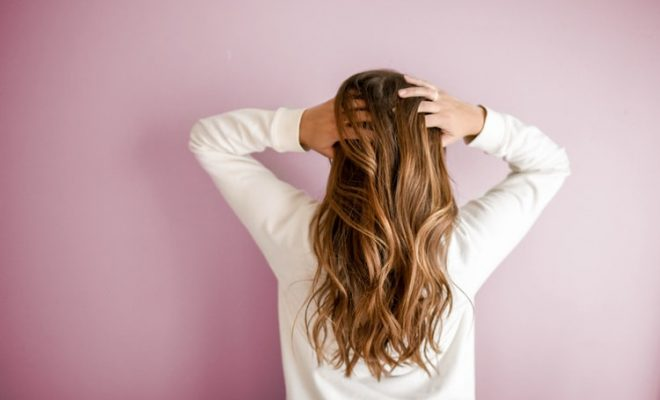 woman facing a wall but playing with her long hair