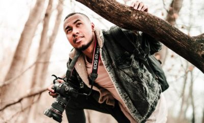 Man ducking under a tree trunk with a camera around his neck