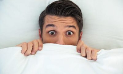 Man hiding under bed sheets,