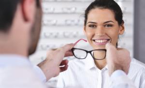 Optometrist put prescription glasses on a lady