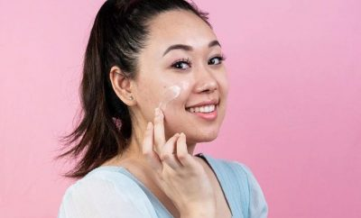 Young woman applying moisturiser to her face