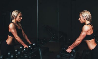 Woman with weights staring in mirror