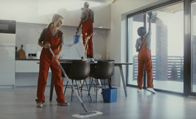 Team of cleaners in red overalls