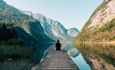 Man sitting at the end of a platform looking at the horizon