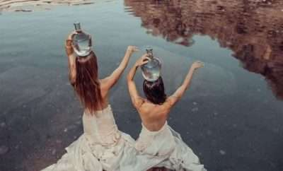 Two women carrying jugs of water on their heads
