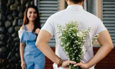 Man hidding flowers behind his back to surprise woman