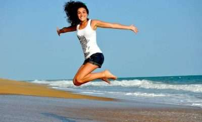 Woman jumping while at the beach